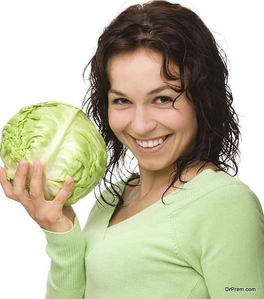 Beautiful young girl with green cabbage