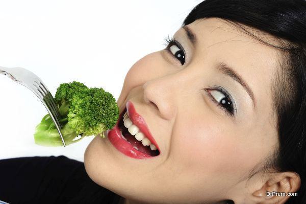 Young asian girl eating broccoli