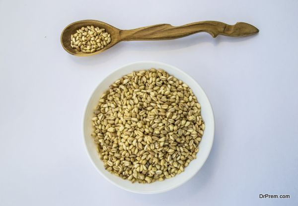 whole wheat in bowl and wooden spoon, horizontal