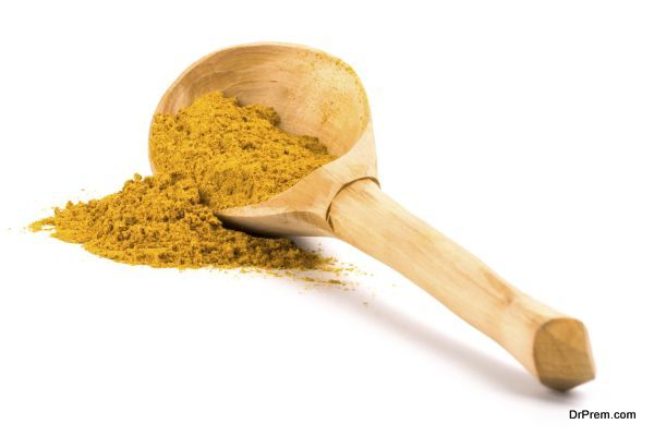 yellow turmeric on wooden spoon