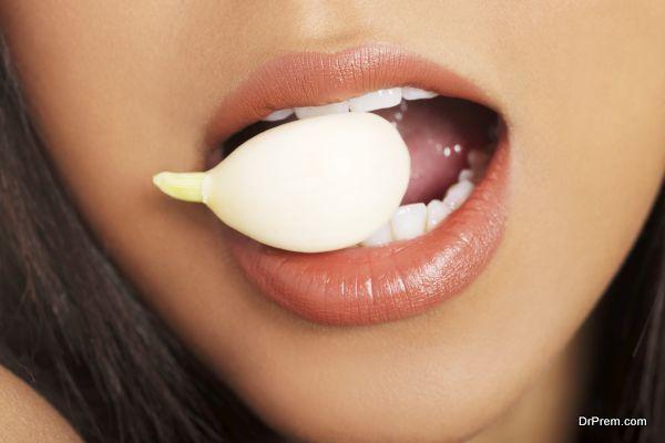 Young beautiful woman eating garlic. Natural antibiotic that fig