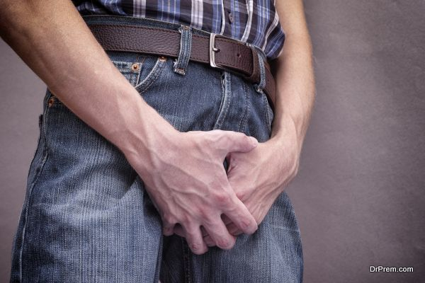 Man in jeans covers his crotch with hands