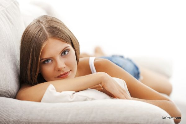 Relaxing on sofa. Beautiful young woman looking at camera while