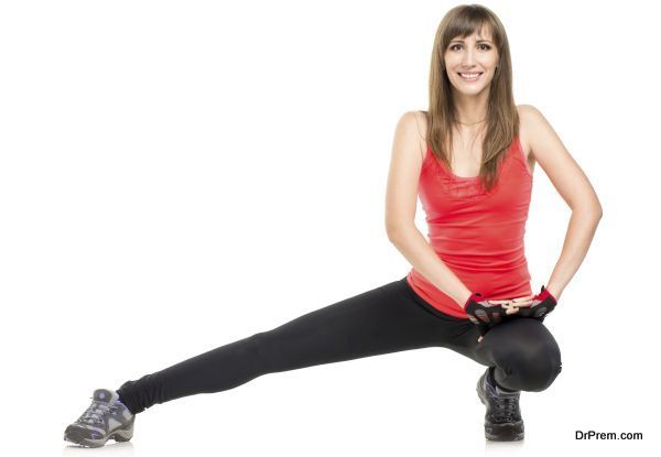 Young fitness woman stretching legs